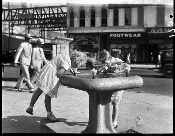 Girls drink from a water fountain on the courthouse square, circa 1930.