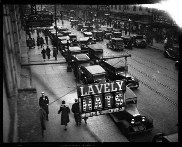 In 1930, the Illinois Power Co. operated the city's buses and streetcars and advertised regularly in the <em>Journal,</em> promoting the advantages of using mass transportation. The photo staff was assigned to capture street scenes that showed congestion, and their photographs were used in the ads. This image shows Monroe Street facing west from Sixth Street, December 16, 1930.