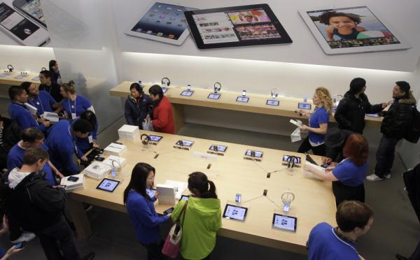 Customers talk with Apple employees, in blue, inside a San Francisco Apple store on Friday, the first day of the launch of the new iPad.