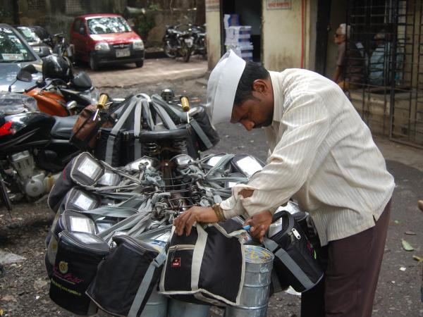 A <em>dabba wallah</em> checks his packages before delivering hot meals to office workers in Mumbai.