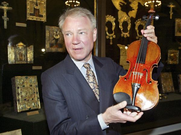 Con man/violin dealer Dietmar Machold holds a (purported) Strad in Moscow in 2003.