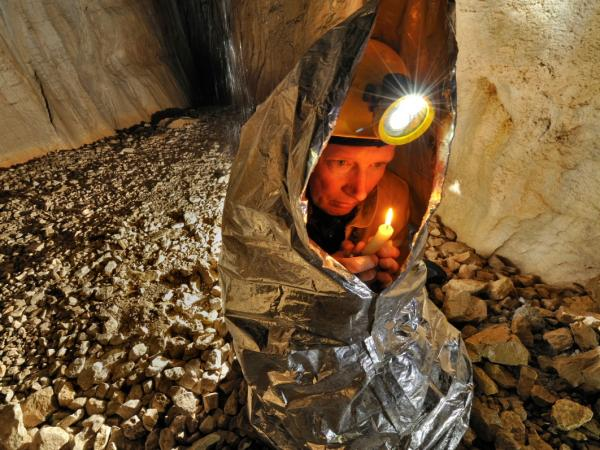 Tim Nixon tries to warm up using the heat from a candle in the Gouffre Berger cave in France.