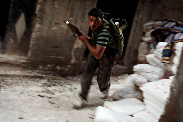 A Free Syrian Army fighter dodges sniper fire in the Salah Al Din neighborhood of Aleppo, Aug. 22.