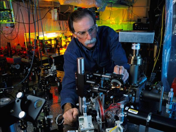 "NIST physicist and Nobel Prize-winner David Wineland adjusts an ultraviolet laser beam used to manipulate ions in a high-vacuum apparatus containing an ""ion trap."" These devices have been used to demonstrate the basic operations required for a quantum computer."