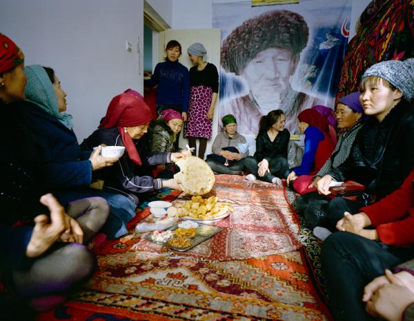 Usunai, the Kuruman family matriarch (center), celebrates a family wedding. The ceremony takes place in a two-bedroom apartment in a newly constructed compound in Wuqiaxian — according to Takayama, a quickly expanding town along a planned highway.