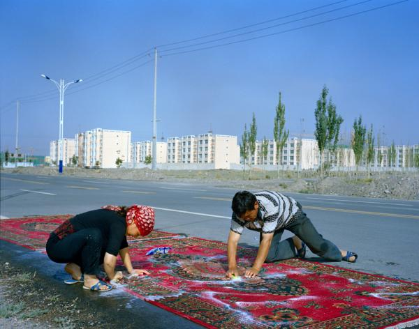 Relatives of the Kuruman family wash carpets by hand. In the background is Wuqiaxian, a growing town along the planned highway. According to Takayama, many of the traditional mud-and-thatch houses will be demolished, and the communities will become more fixed in an urbanizing town.