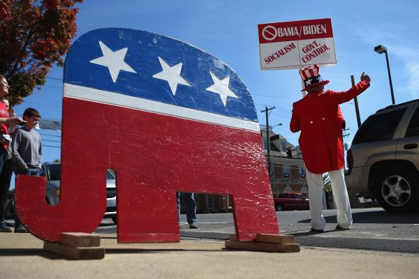 Sam Adams gives a thumbs up to cars that honk in support of his anti-Obama sign.