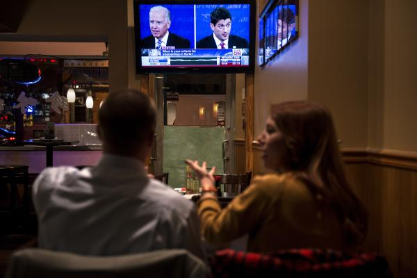 A couple watches the vice presidential debate at Wok and Roll restaurant in Washington, D.C.