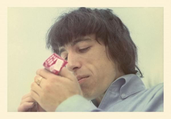 Bill Wyman lighting a cigarette.