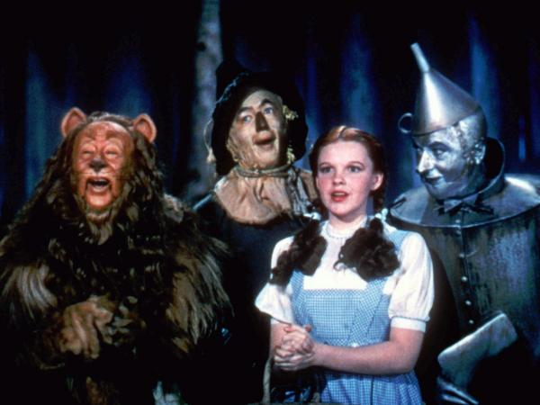 Bert Lahr as the Cowardly Lion, Ray Bolger as the Scarecrow, Judy Garland as Dorothy, and Jack Haley as the Tin Man in <em>The Wizard Of Oz</em>.