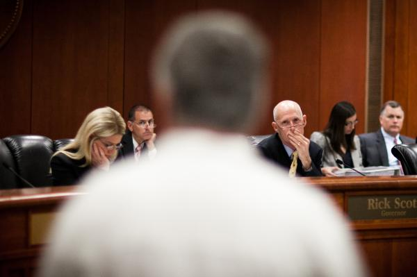 Florida Gov. Rick Scott listens to testimony from felons attempting to restore their right to vote at a clemency hearing in Tallahassee, Fla., in June.