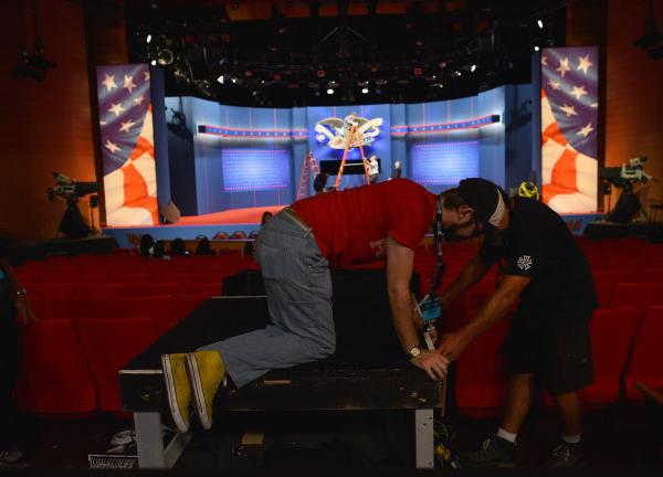 Crew work to put finishing touches on the stage a day ahead of the third and final presidential debate at Lynn University in Boca Raton, Fla.
