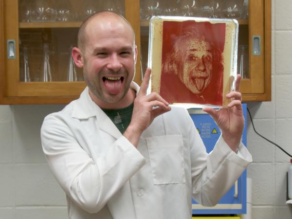 "Zachary Copfer poses with his first ""bacteriograph,"" a portrait of Albert Einstein."