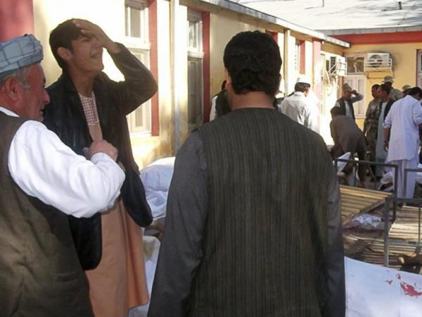 Men mourn beside the bodies of victims from today's suicide bomb attack in Maymana, Afghanistan.