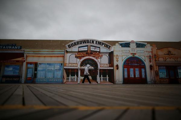 A man walks down a seemingly empty boardwalk as Hurricane Sandy approaches on Sunday in Atlantic City, N.J.