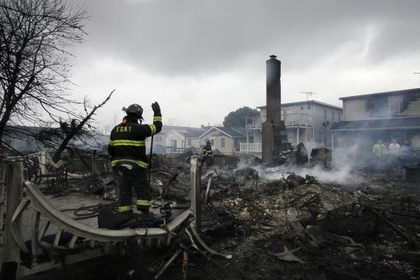 A firefighter surveys the smoldering ruins of a house in the Breezy Point section of New York.