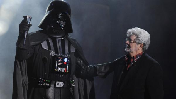 "In this Oct. 15, 2011 file photo, ""Darth Vader"" accepts the Ultimate Villain award from <em>Star Wars</em> creator George Lucas during the 2011 Scream Awards."