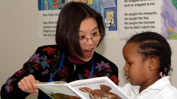 A Read Aloud Delaware volunteer reads to a student.