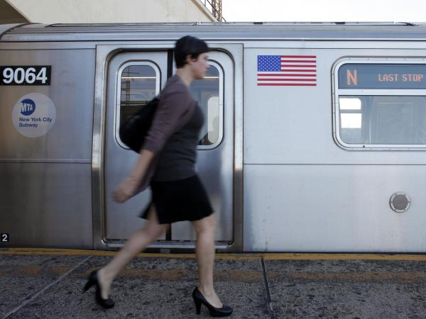 A commuter walks down the platform before boarding a Manhattan-bound N train at Astoria-Ditmars Boulevard station in the Queens borough of New York.