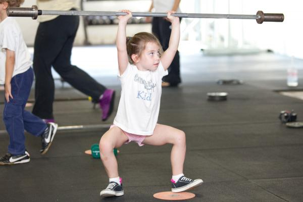 Rose MacDermott, 6, lifts a barbell above her head as part of her CrossFit exercise.