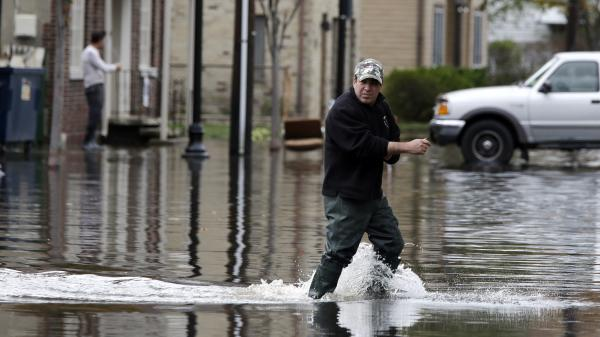 A man crosses a flooded street in the wake of Superstorm Sandy on Thursday in Little Ferry, N.J. Surprise coastal surge floods caused by the storm battered Little Ferry, Moonachie and some other towns along the Hackensack River in Bergen County, all areas unaccustomed to flooding.