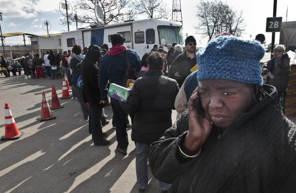 Evangean Pugh, far right, talks on a phone as she waits in line to apply for recovery assistance at a FEMA processing center in Coney Island, in the Brooklyn borough of New York.