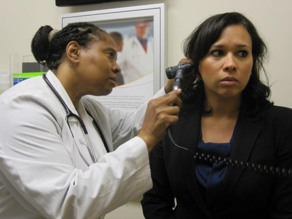Dr. Wanda Simmons-Clemmons examines Dawn Antonelli at the PromptCare urgent care clinic.