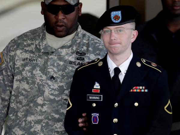Army Pfc. Bradley Manning (right) is escorted out of a courthouse in Fort Meade, Md., on June 25, 2012. His lawyer announced that Manning, who is accused of leaking classified information to WikiLeaks, had agreed to plead guilty to lesser charges.