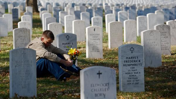 Marine Corps Capt. Jeff Cliffe, sat to reflect Sunday next to the grave of his grandfather and grandmother at Arlington National Cemetery in Virginia.