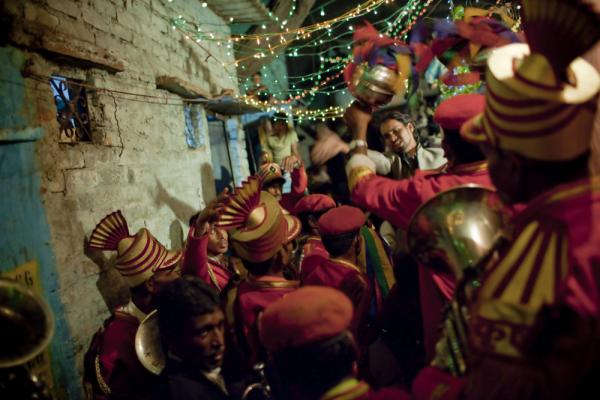 A wedding band gathers around the entrance of the groom's house in one of the colony's many celebrations. During the run-up to the event, the streets flood with people; rupees are tossed in the air; and drum processions compete with one another for speed and intensity.