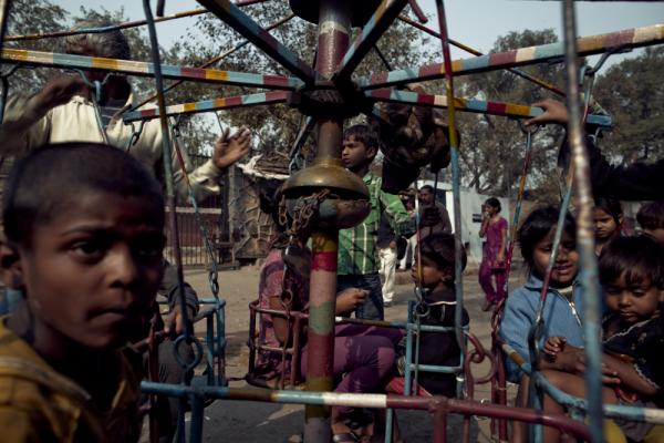 Young children gather on a spinner as an old man turns the wheel.