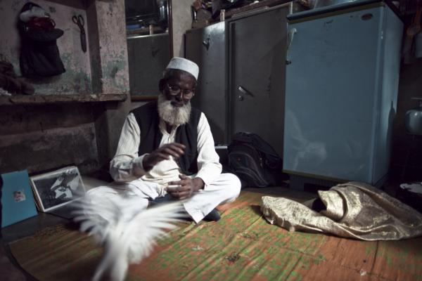 Hussein, the oldest remaining magician in the colony, with one of his two doves.