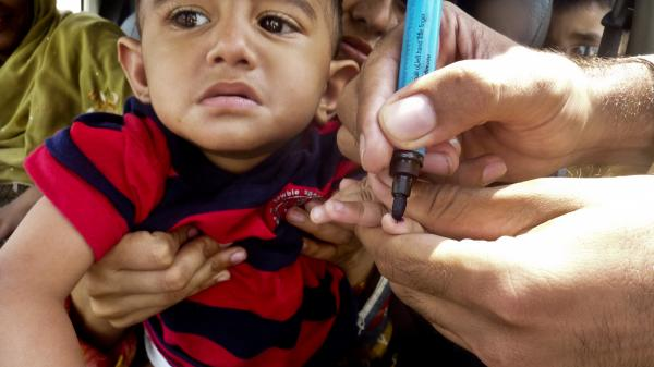 A health worker in Pakistan marks a child's finger with ink after giving him the polio vaccine.