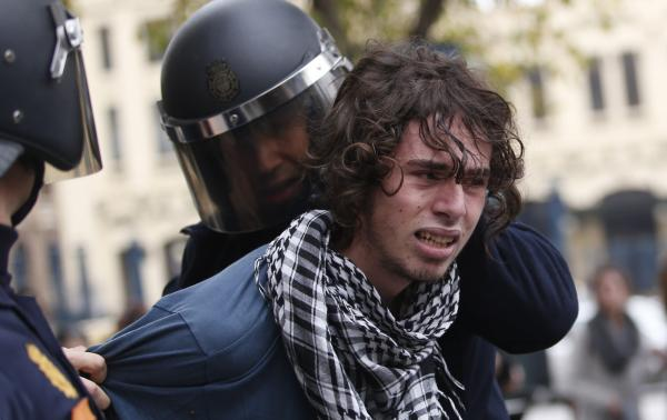 Riot policemen arrest a protester in Valencia on Wednesday during a general strike .