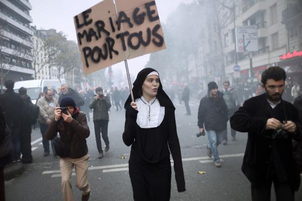 "A woman holds a sign ""marriage for all"" as she attends a demonstration called by unions in Paris."