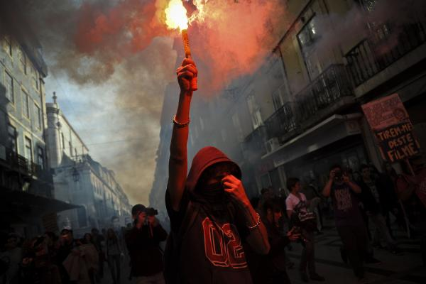 A protester holds a flare during a demonstration in Lisbon.