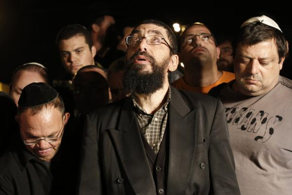 Family and friends of Aaron Smadja, one of the three Israelis killed by a rocket fired from Gaza, mourn during his funeral at a cemetery in the southern Israeli town of Kiryat Malachi on Thursday.