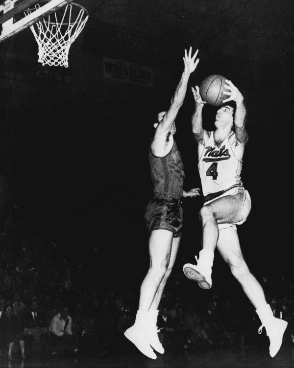 Dolph Schayes (right) of the Syracuse Nationals drives in to score in a March 1959 NBA playoff game.