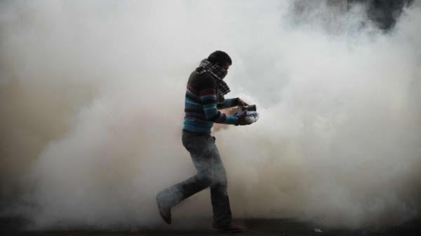 A cloud of tear gas surrounds a protester earlier today near Cairo's Tahrir Square.