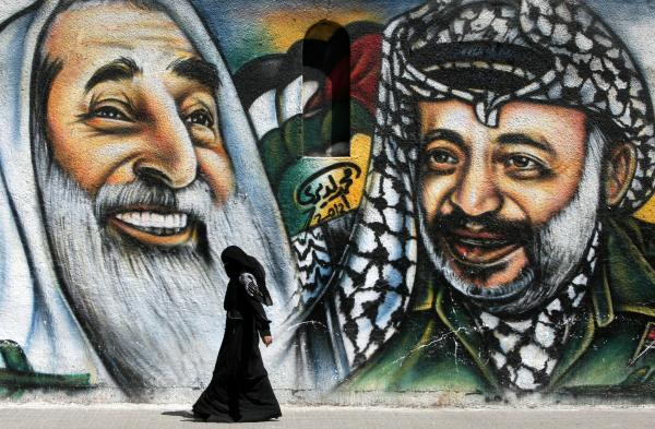 A Palestinian woman walks past a mural depicting late Palestinian leader Yasser Arafat, right, and late Hamas spiritual leader Sheikh Ahmed Yassin, left.
