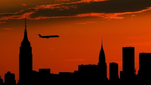 A plane flies past the Manhattan skyline at sunset.