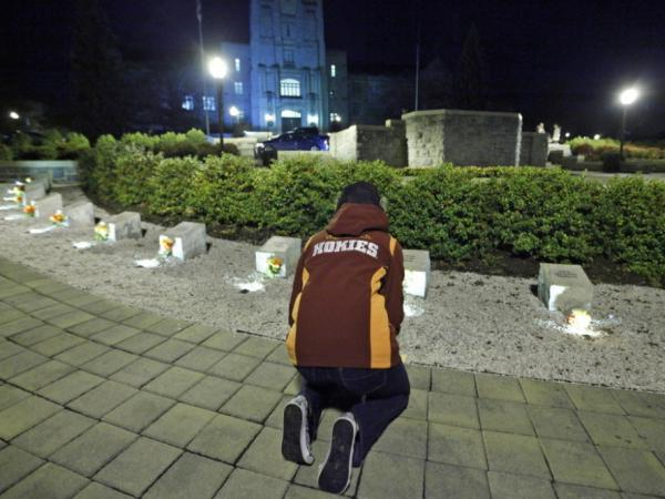 A student paused Thursday evening at the memorial for the victims of the 2007 massacre at Virginia Tech. There was another vigil last night, following Thursday's killing of a campus police officer.