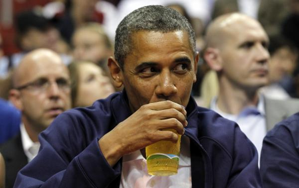 President Obama drinks a beer — that's presumably <em>not</em> from the White House — as he watches the U.S. men's basketball team play Brazil in an Olympic exhibition game in July.