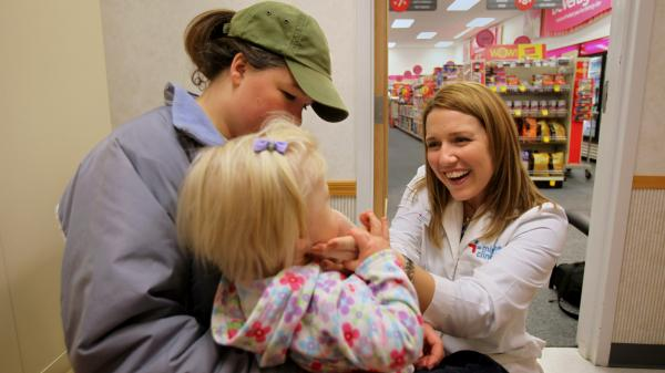Nurse practitioner Leah Martin examines 13-month-old Mia Beavers at a CVS clinic in Chagrin Falls, Ohio, in early 2009. Mia's mother, Brittany, looks on.