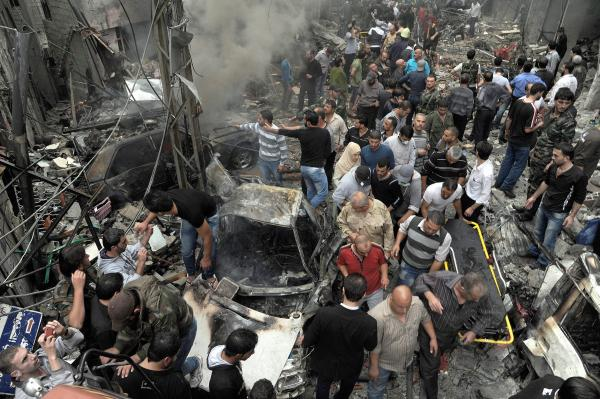 Syrians gather at the site of a car bombing Monday that killed 11 people and wounded dozens in Damascus, according to the SANA news agency, which provided the photo. The violence in the city was described as some of the worst in recent months.