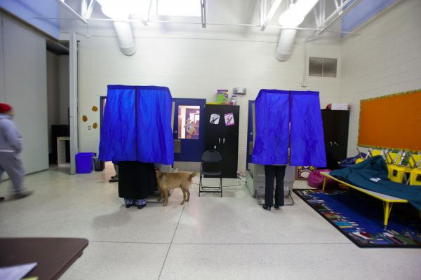 A woman is accompanied by her dog as she casts her vote on in South Philadelphia, Pa.