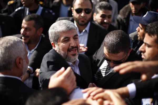 The exiled Hamas chief Khaled Mashaal shakes hands with supporters upon his arrival at Rafah crossing in the southern Gaza Strip.