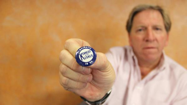Ken Rudin holds up a pin from the 1964 campaign season in Illinois. Rudin has a collection of over 60,000 political buttons, and everyone at NPR knows that if you see a good button, grab it for Ken.