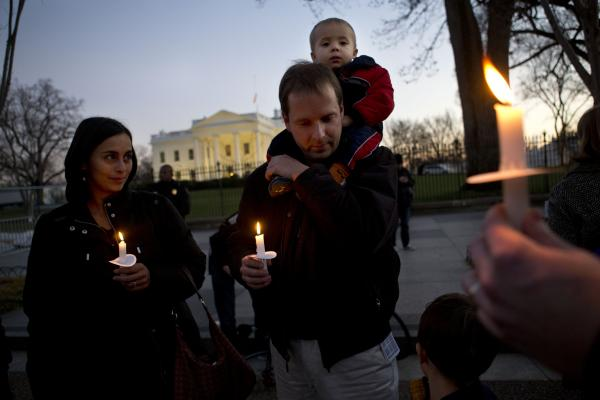 Fabiola Cordova, left, her husband Chris Homan with their son Leo, 2, attend a candlelight vigil in front of the White House on Friday.