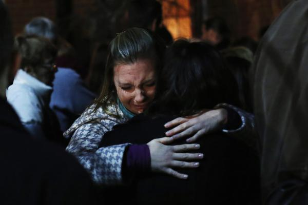 People grieve outside the overflow area of a vigil at the Saint Rose of Lima church in Newtown.